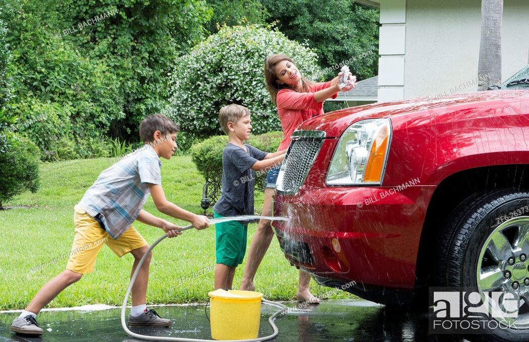 Stock Photo: Single mother washing car at home with her two children in driveway with hose MR-11, MR-12, MR-13 Model Released.