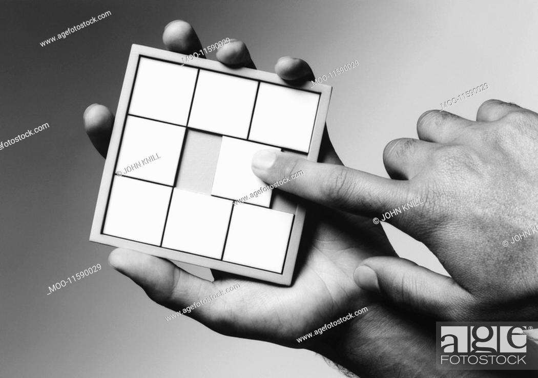 Stock Photo: Hands holding slide puzzle b&w close-up.