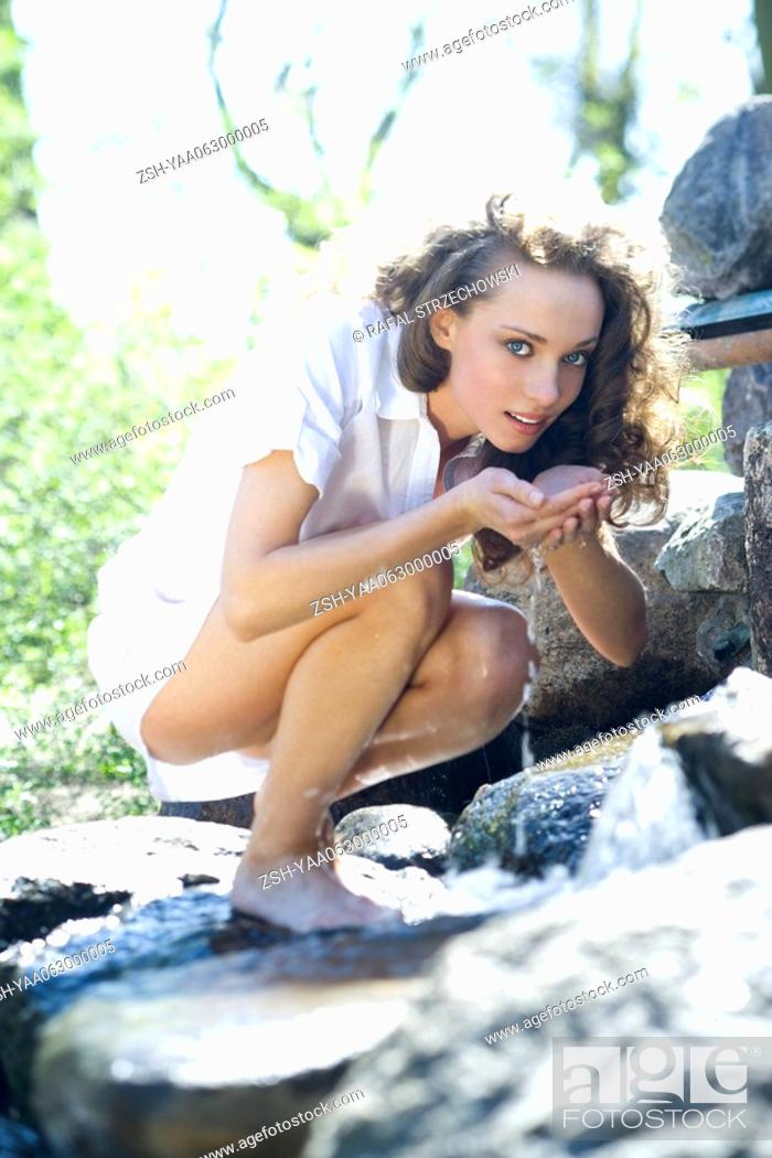 Stock Photo: Young woman crouching on rocks, holding water in cupped hands, looking at camera.