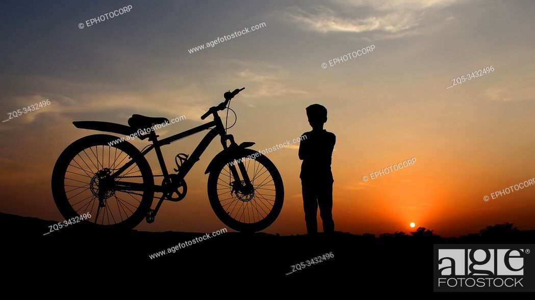 Stock Photo: PUNE, MAHARASHTRA, INDIA, 01 June 2019, Silhouette of boy and cycle against setting son.