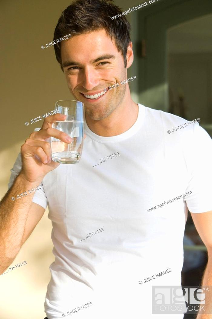 Stock Photo: Young man with glass of water, smiling, portrait, close-up.