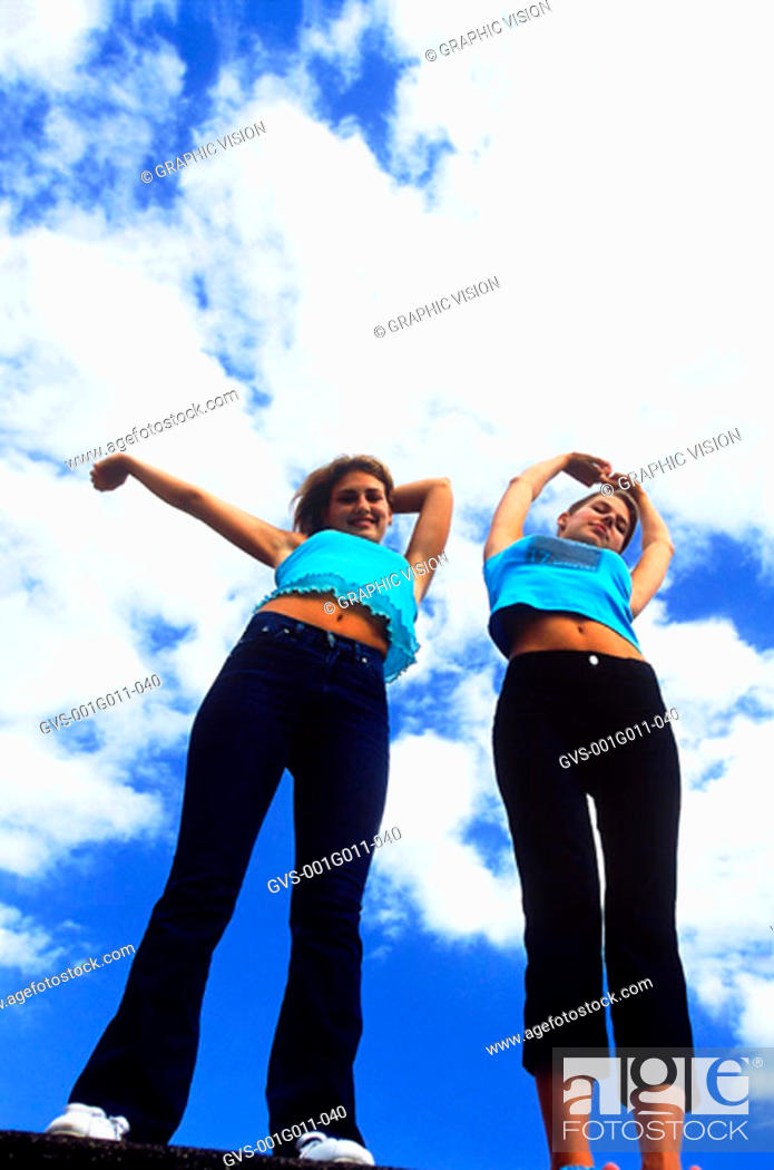 Stock Photo: Low angle view of two young women stretching.