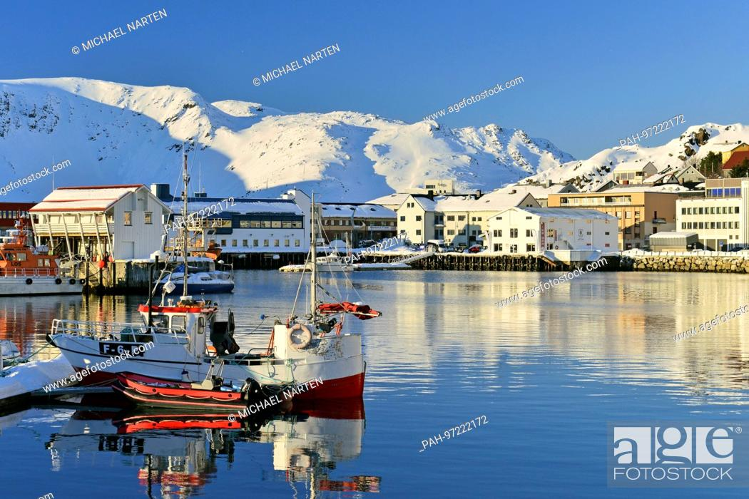 Stock Photo: A small ship with a red dinghy in Honningsvåg's harbour surrounded by snow-covered mountains in the background, 7 March 2017 | usage worldwide.