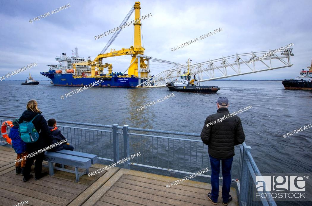 """Imagen: 04 March 2021, Mecklenburg-Western Pomerania, Wismar: Passers-by watch from the pier the Russian pipe-laying ship """"""""Akademik Tscherski"""""""" being towed by tugs."""