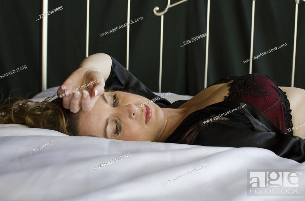 Imagen: Sad woman laying down in bed hand over forehead.