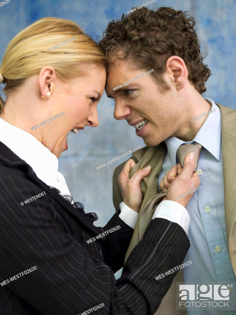Stock Photo: Businesswoman grabbing man by tie, shouting, side view, close-up.