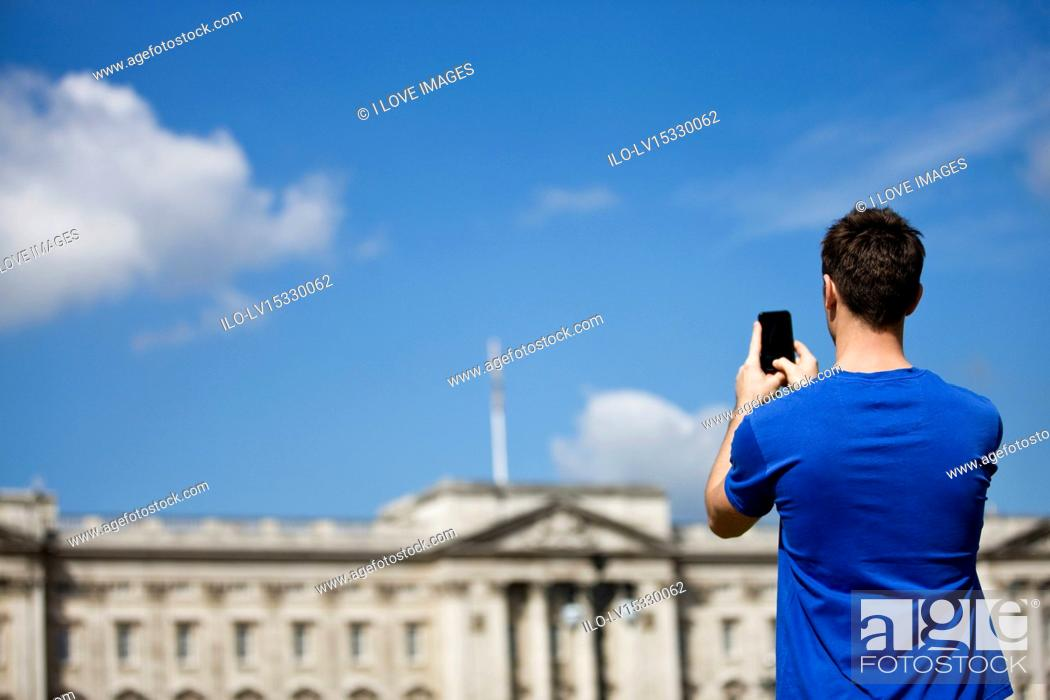 Stock Photo: A young man taking a picture of Buckingham Palace.