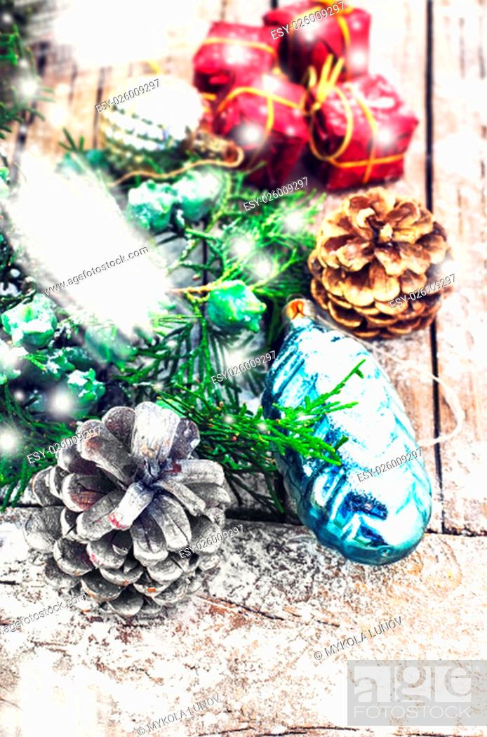 Stock Photo: Christmas decorations under the branches of fir tree on snowy wood plank.