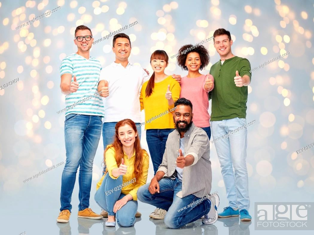 Stock Photo: diversity, race, ethnicity and people concept - international group of happy smiling men and women showing thumbs up over holidays lights background.