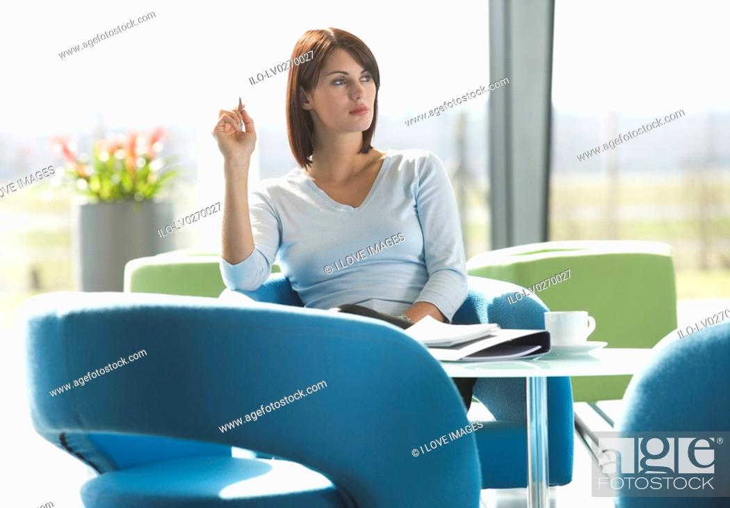 Stock Photo: A woman sitting at a table with notes and papers, thinking.