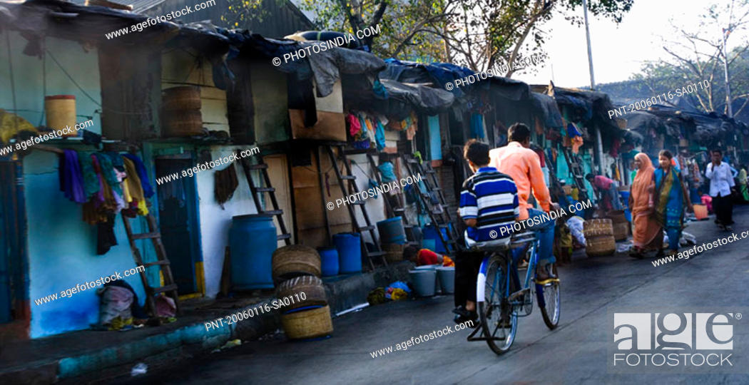 Stock Photo: Rear view of two men cycling on the street, Mumbai, Maharashtra, India.