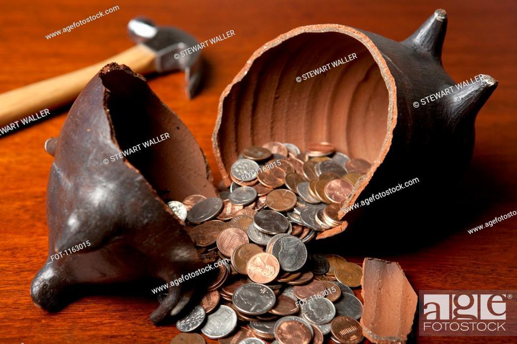 Stock Photo: Piggy bank broken open by hammer.