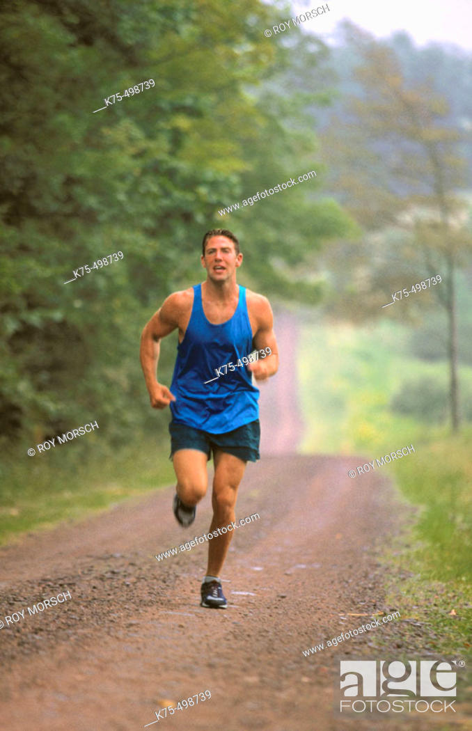 Stock Photo: Man running down country road.
