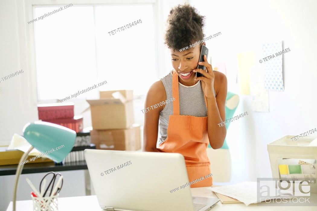 Imagen: Young woman in home office on the phone.