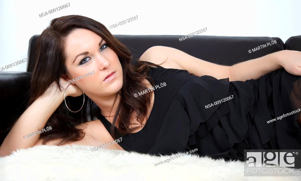 Stock Photo: beautiful young woman lying on sofa.
