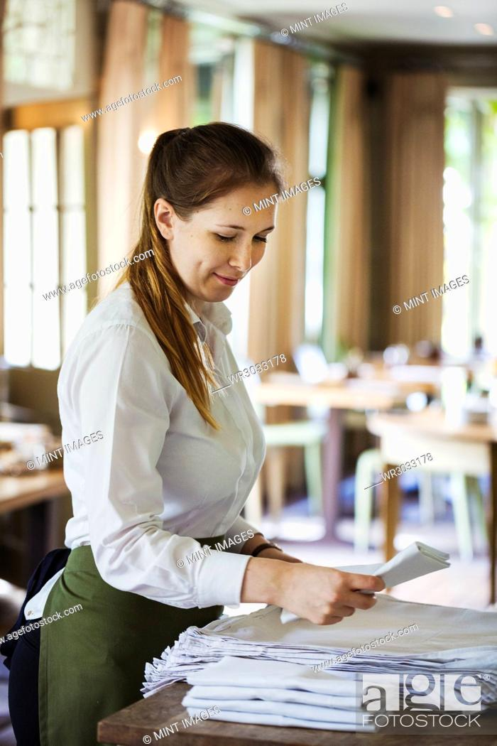 Stock Photo: Woman wearing apron standing at a table in a restaurant, folding napkins.