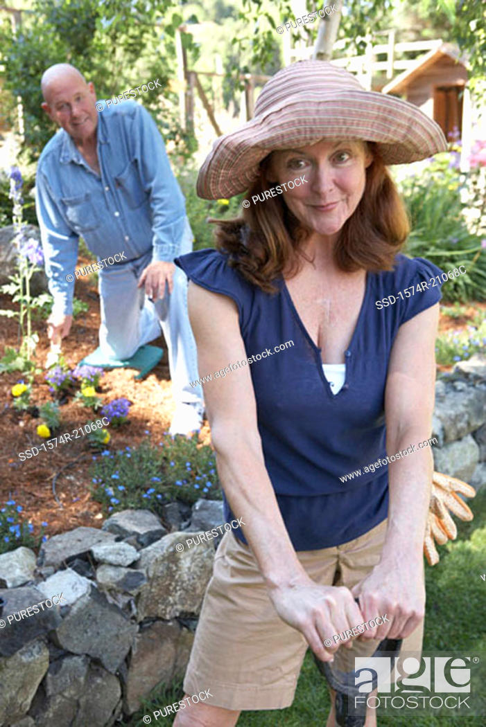 Stock Photo: Portrait of a mature woman with a shovel and a mature man kneeling in the background.