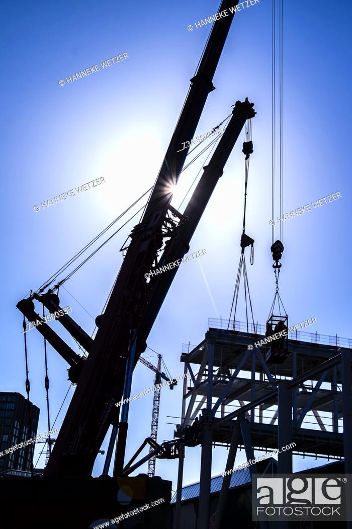 Photo de stock: Two workmen hoisted up at a construction site at Strijp-S, Eindhoven, The Netherlands, Europe.