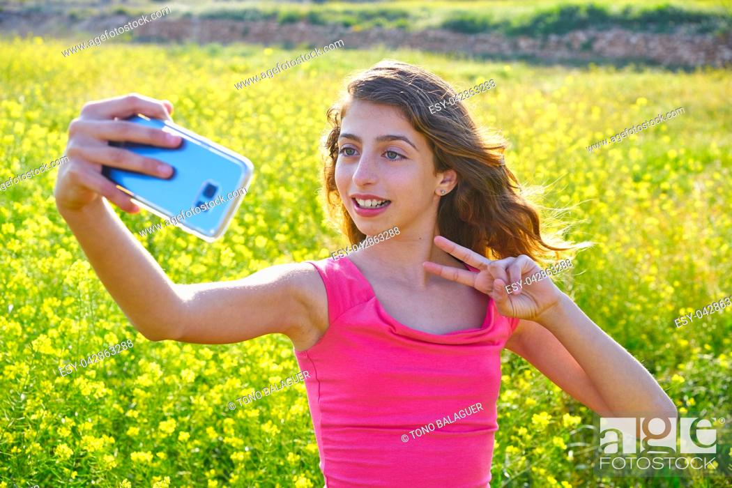 Photo de stock: Teen girl serfie video photo in spring meadow gesturing.