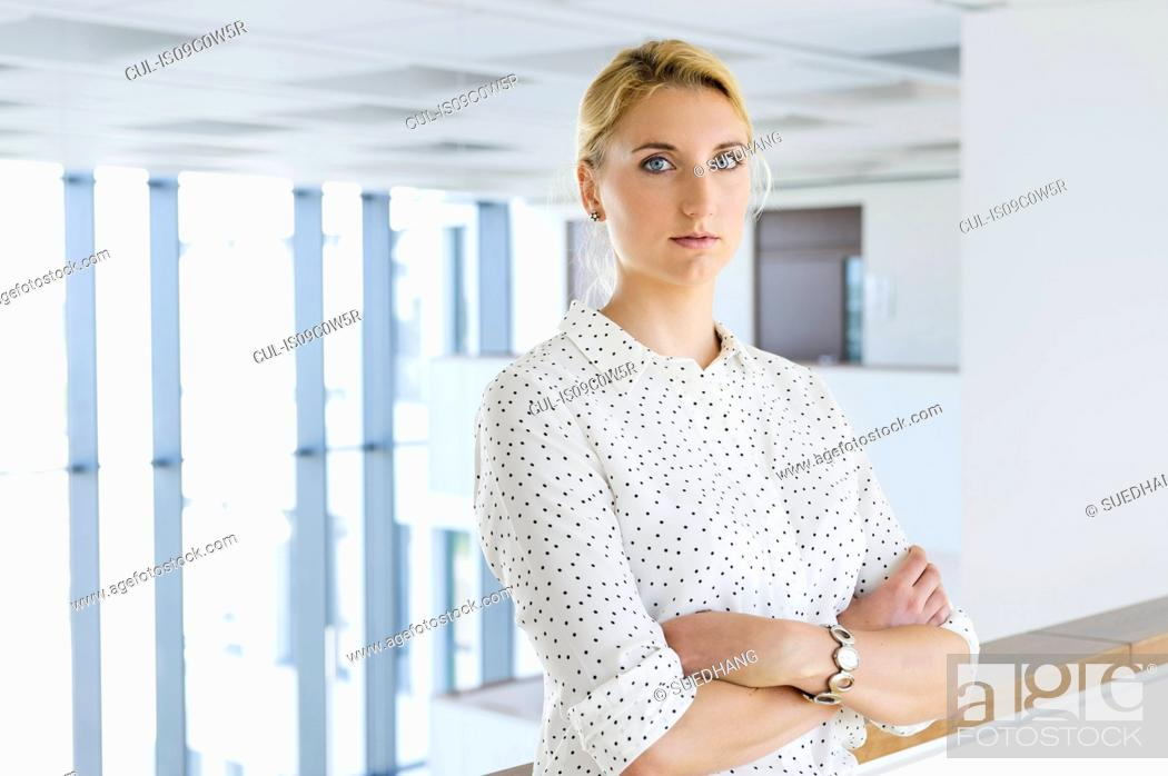 Stock Photo: Businesswoman taking break in office corridor.