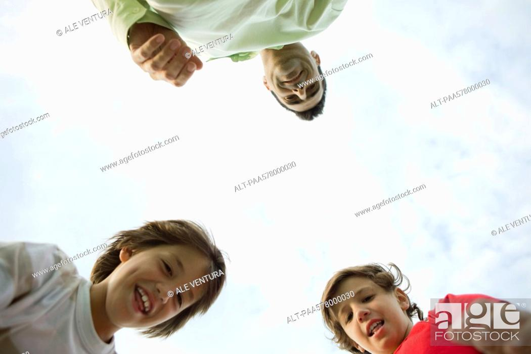 Stock Photo: Father and sons outdoors, low angle view.