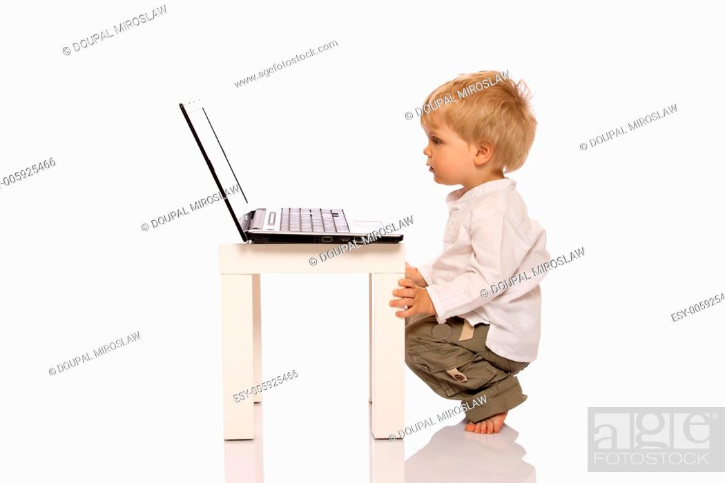 Stock Photo: Young boy looking at a laptop on a stool. Isolated on white background.