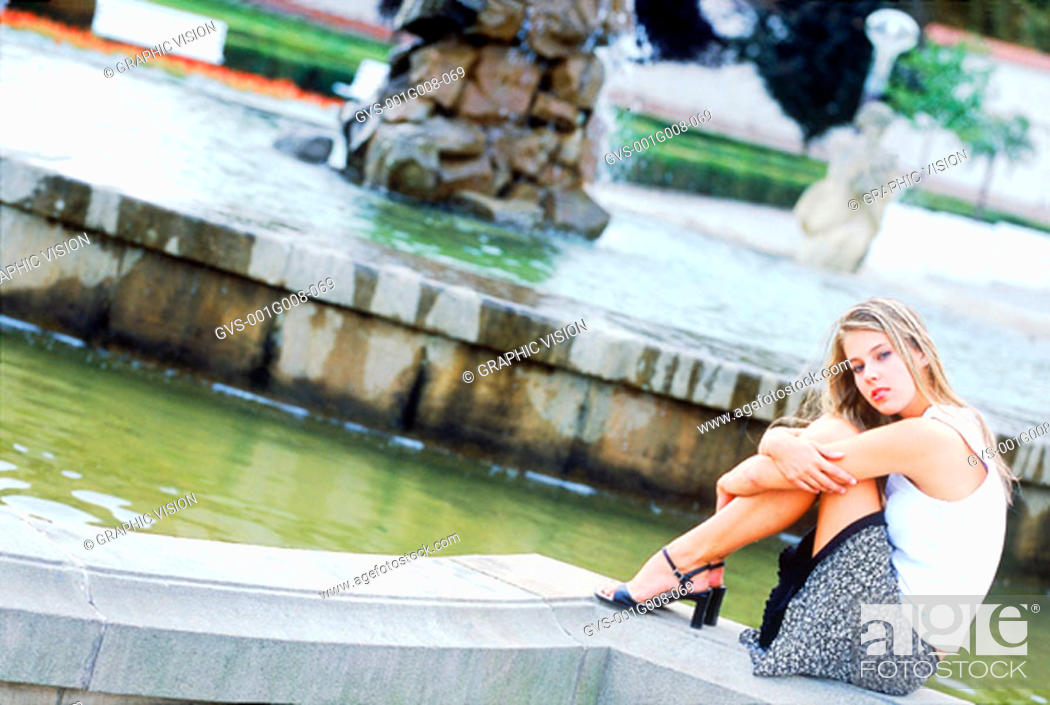 Stock Photo: Young woman sitting on a fountain wall outdoors.