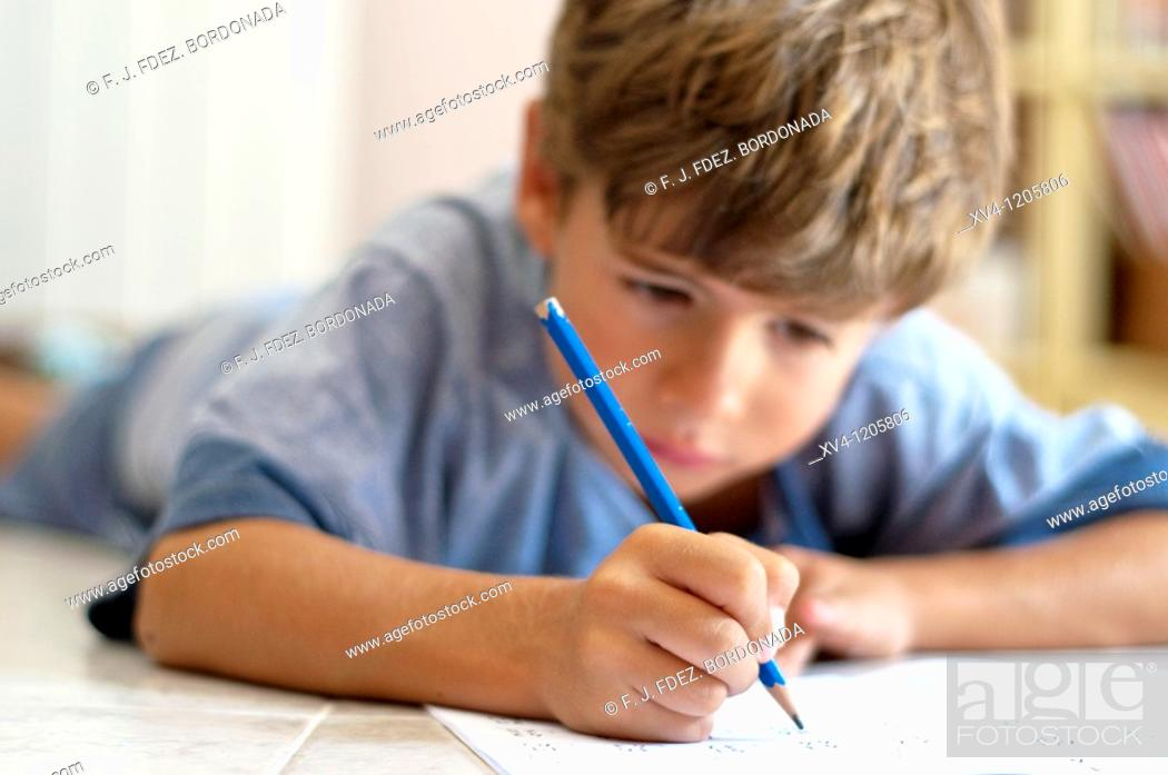 Stock Photo: Boy studing at home.