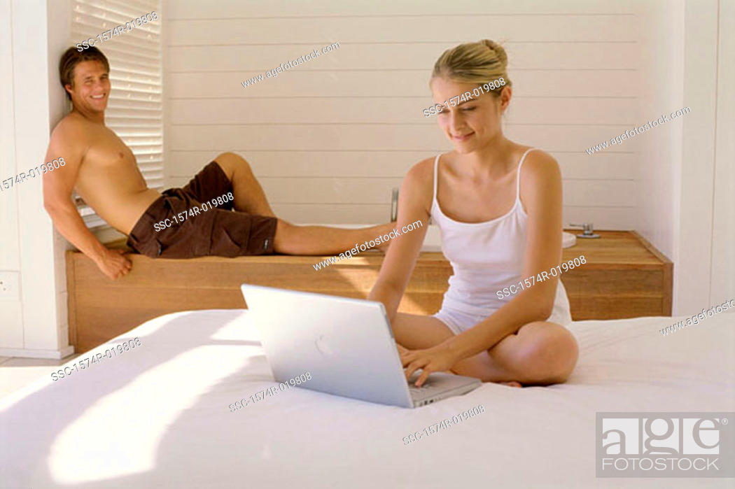 Stock Photo: Young woman working on a laptop with a young man sitting behind her.