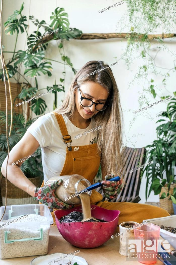 Stock Photo: Young woman working at table in a small gardening shop.