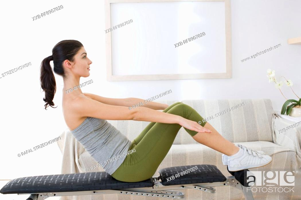 Stock Photo: young woman exercising at home.