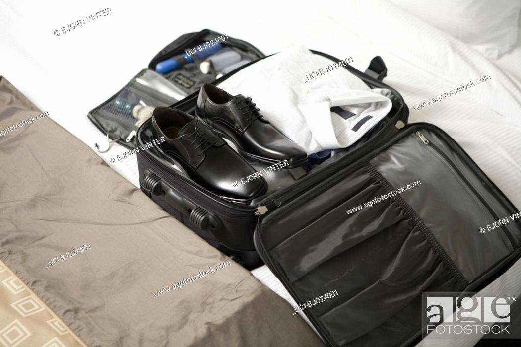 Stock Photo: Businessman's packed suitcase on bed.