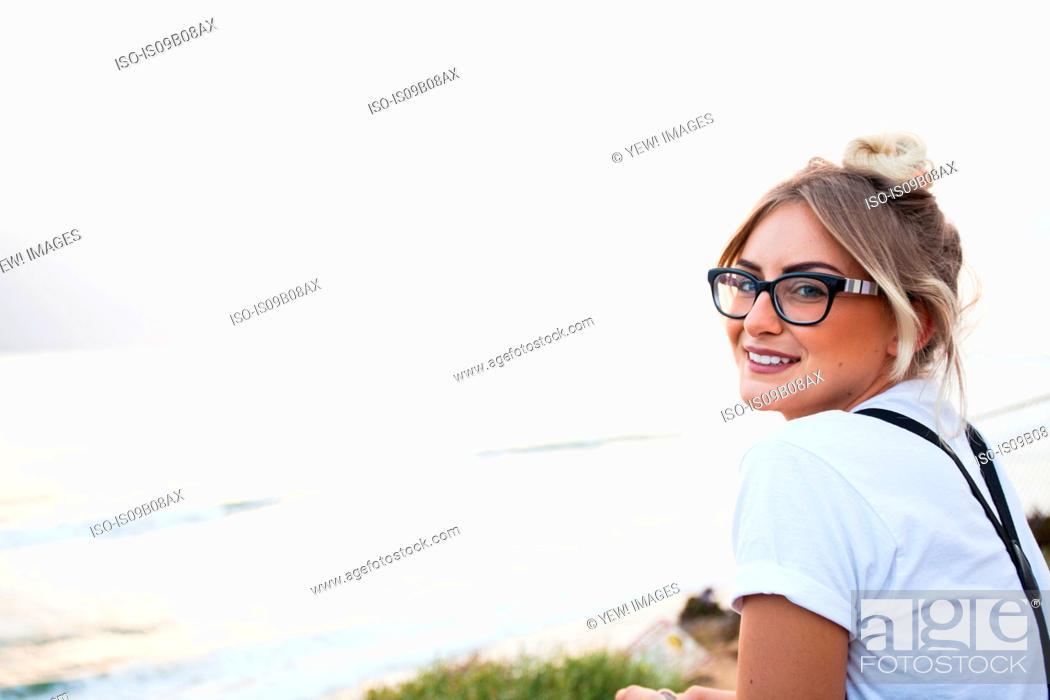 Stock Photo: Woman by ocean looking over shoulder at camera smiling, Encinitas, California, USA.