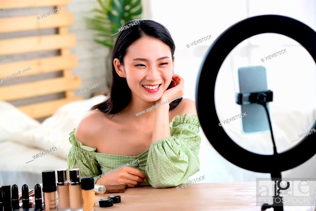 Stock Photo: Young women live online makeup.