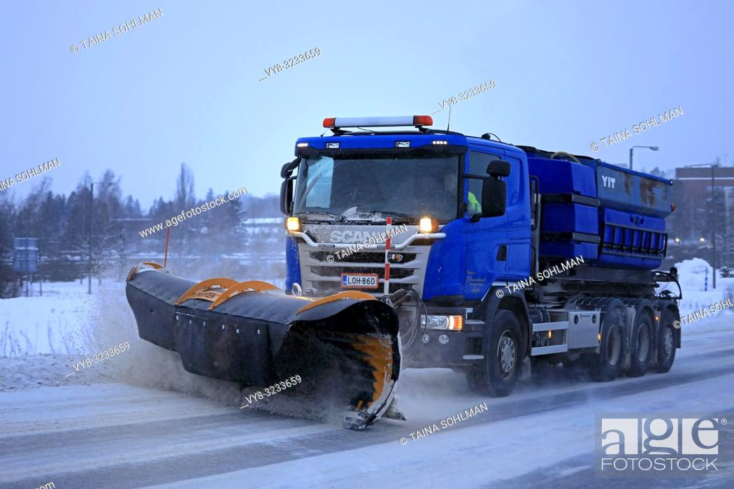 Stock Photo: Salo, Finland - January 26, 2019: Blue Scania truck of equipped with snowplow clears a snowy road in suburban area on a winter afternoon.