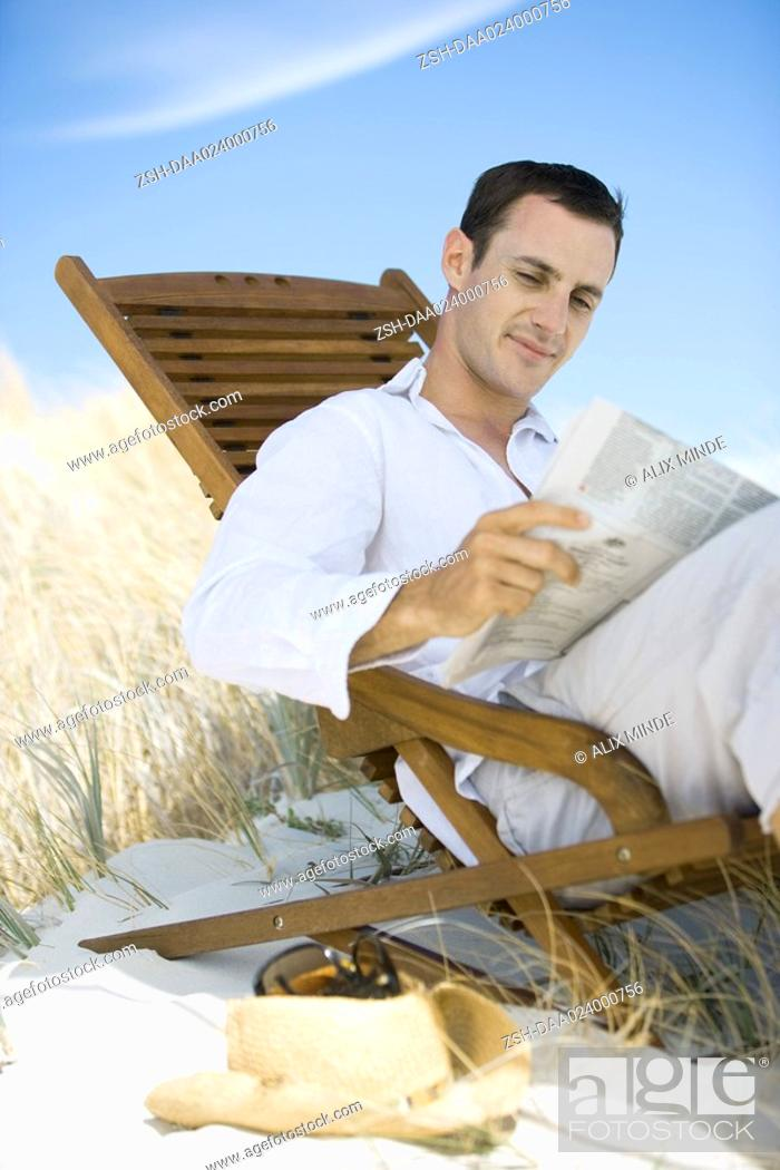 Stock Photo: Young man sitting in deck chair on beach, reading newspaper.