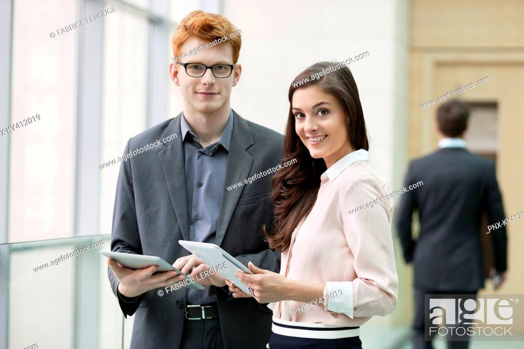 Stock Photo: Portrait of business executives using digital tablets in an office.