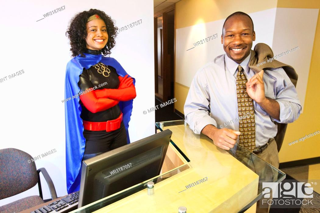 Stock Photo: A black businesswoman office super hero and her black businessman partner in their office.