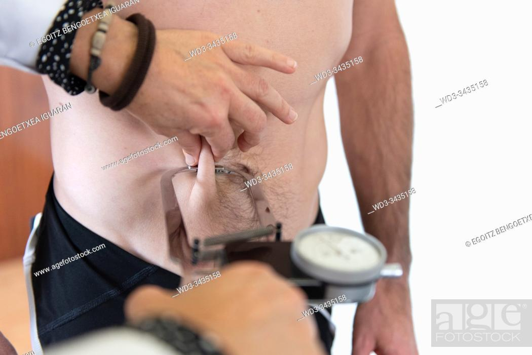 Stock Photo: A female nutritionist measuring the body fat ratio of an athletic man by using a caliper. Plicometer.