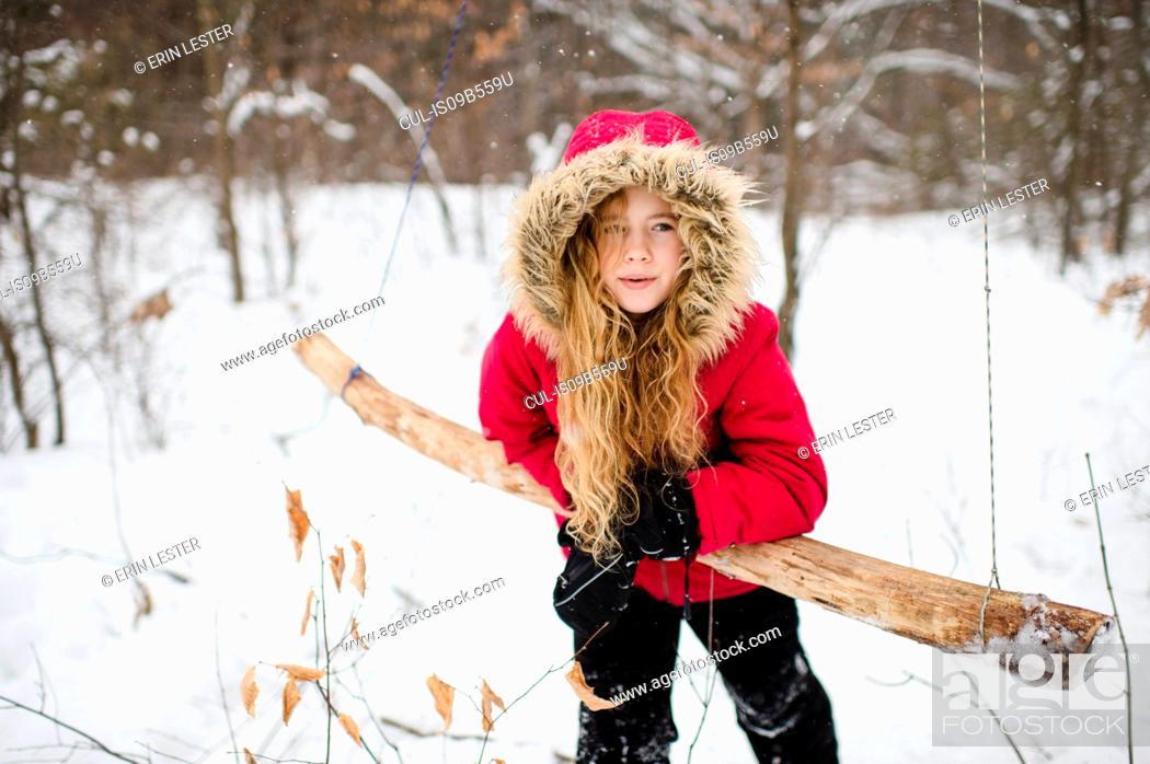 Photo de stock: Girl leaning on wooden swing in woods.