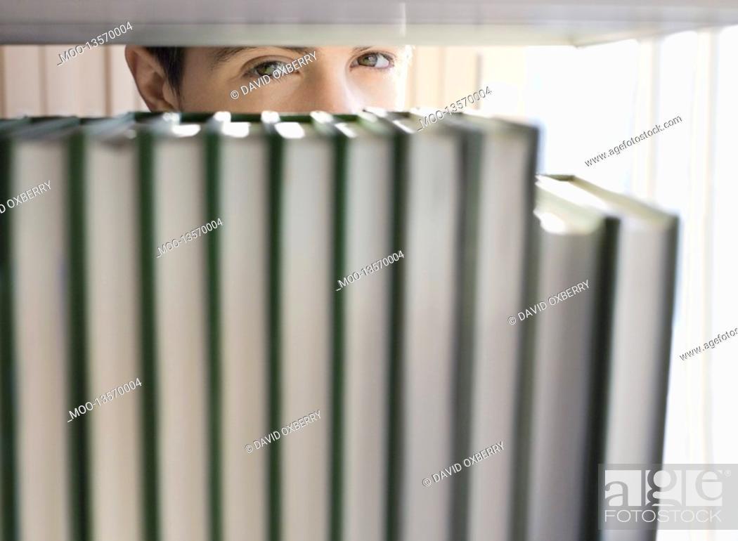 Stock Photo: Yong man peeking from behind books on shelf.
