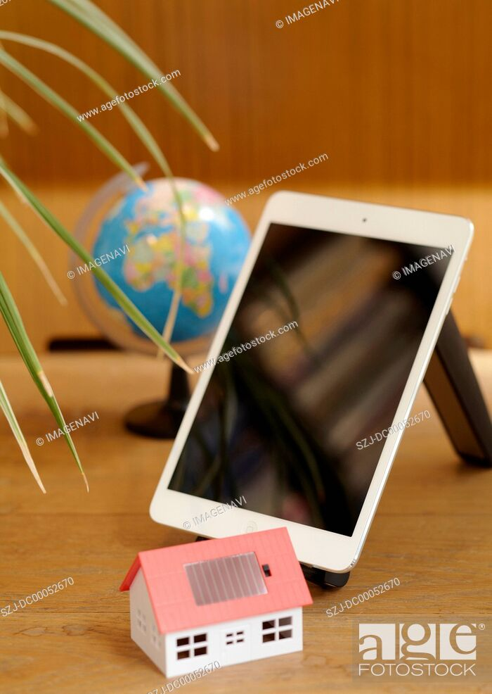 Stock Photo: Tablet PC and a model of solar house.