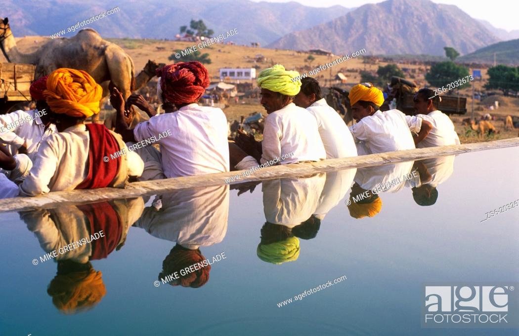 Imagen: Colourful turbans reflected in a water tank , Pushkar Camel Fair , Rajasthan , India.