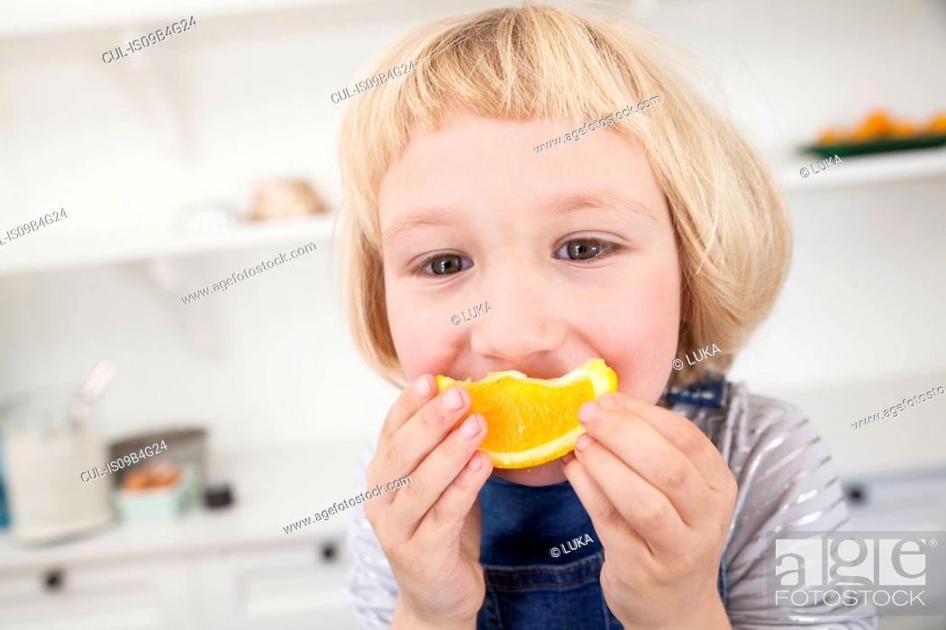Stock Photo: Portrait of cute girl in kitchen holding orange slice to her mouth.