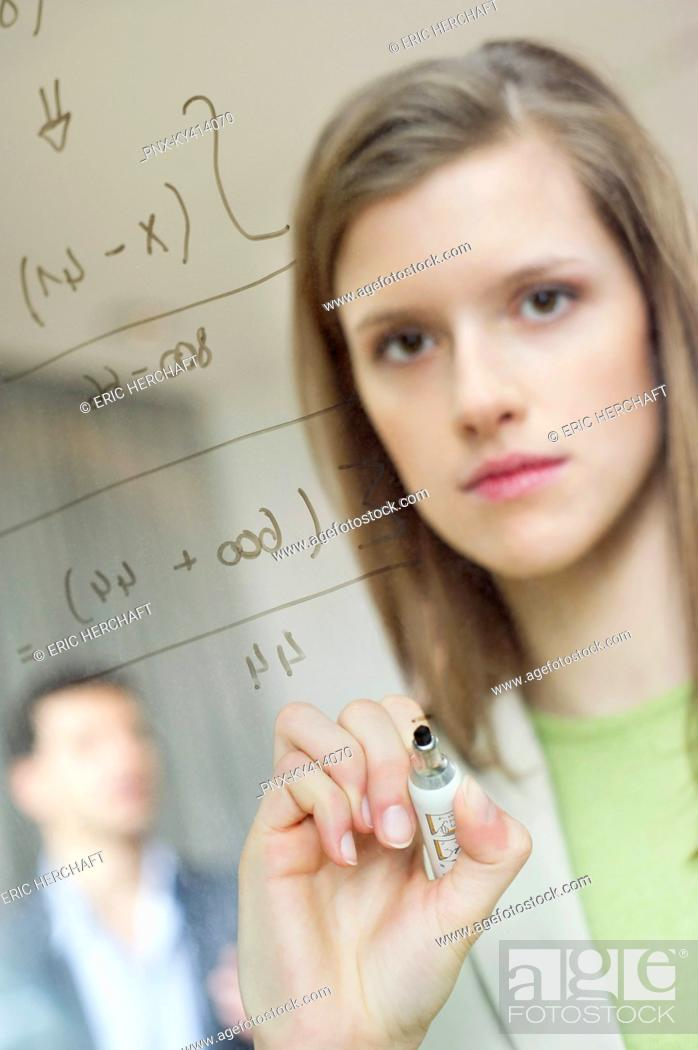 Stock Photo: Businesswoman writing numeric figures on a glass surface.