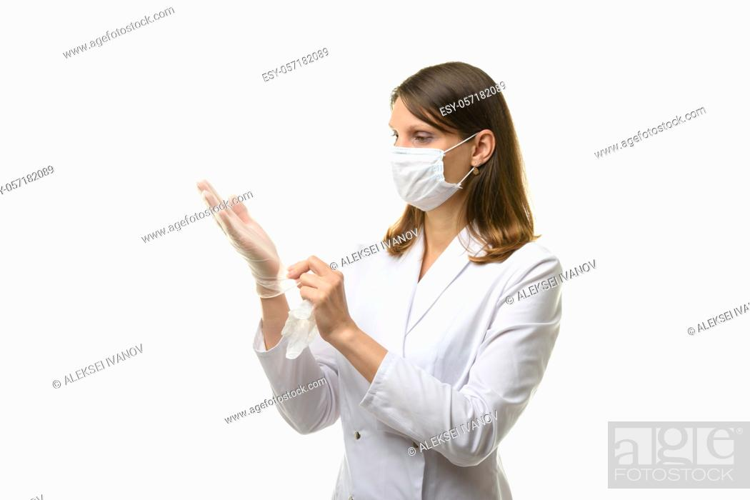 Stock Photo: Girl doctor puts on transparent medical gloves on her hands.