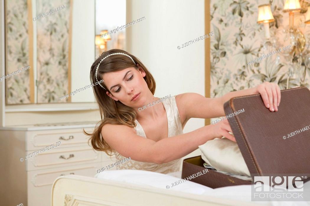 Stock Photo: young woman looking into case.