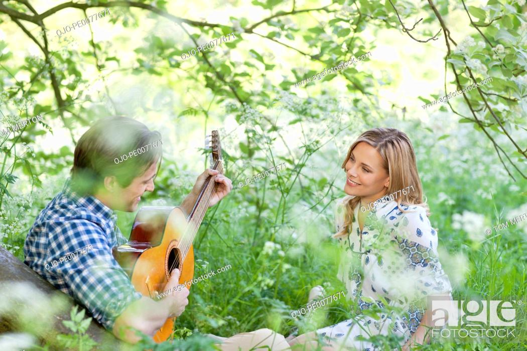 Stock Photo: Man playing guitar for girlfriend in field of flowers.