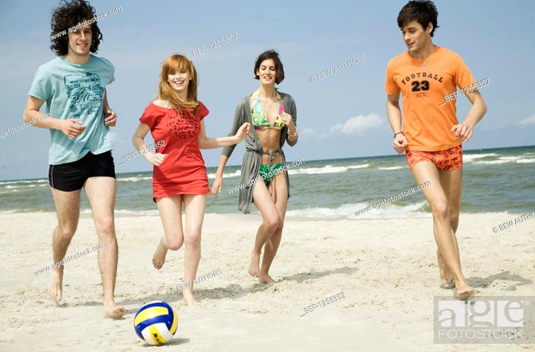 Stock Photo: Four friends playing volleyball on the beach.