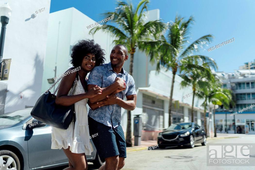 Photo de stock: USA, Florida, Miami Beach, happy young couple crossing the street.